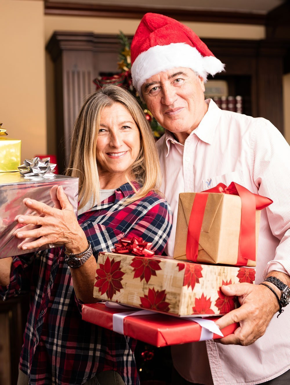 Husband & Wife holding wrapped Christmas gifts